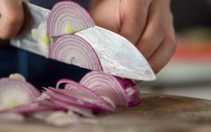 Hand cutting red onions on cutting board.