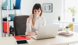 Woman drinking coffee and looking at laptop in home office.