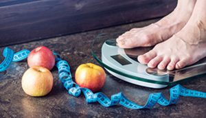 Person standing on scale, apples, and tape measure to illustrate warding against stroke.