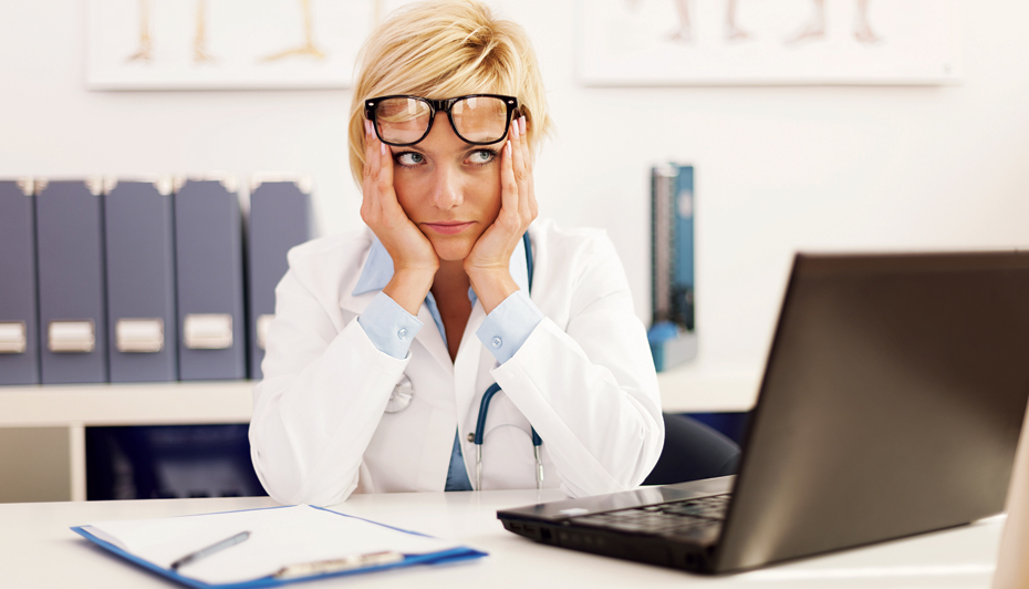 Frustrated healthcare worker seated at desk