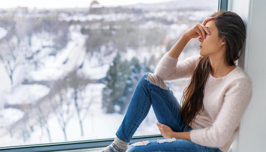 Sad woman sitting at window in winter