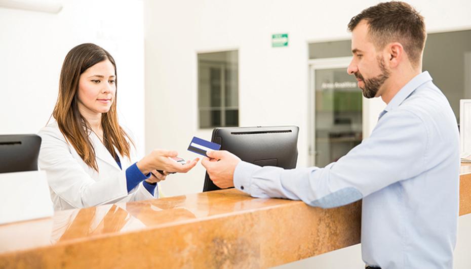 Patient handing payment to front desk worker