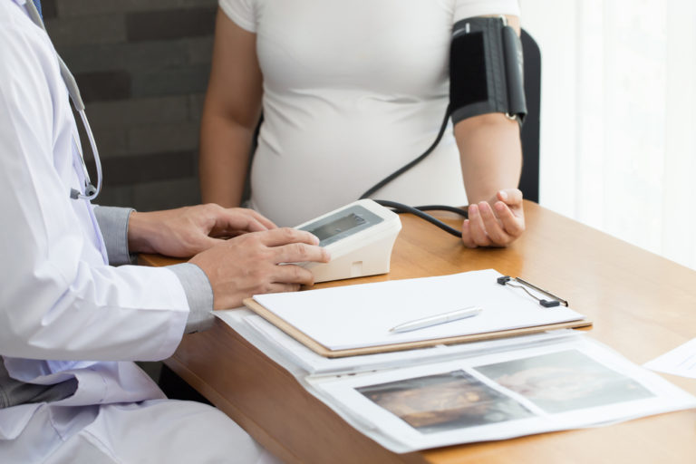 pregnant woman getting blood pressure taken
